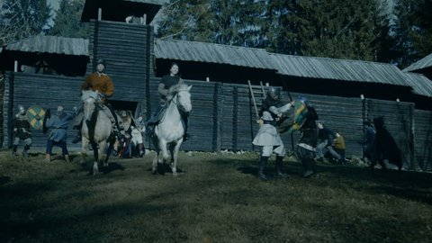 Medieval Battle Where Vikings Attack Wooder Fortress, Villagers Defend and Fight. Women on Horses Run for Their Lives. Medieval Reenactment. Shot on RED EPIC-W 8K Helium Cinema Camera.