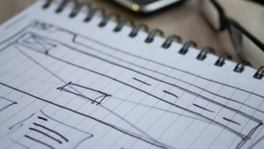Web designer draws the layout of the site in his book. | Shutterstock HD Video #33541459