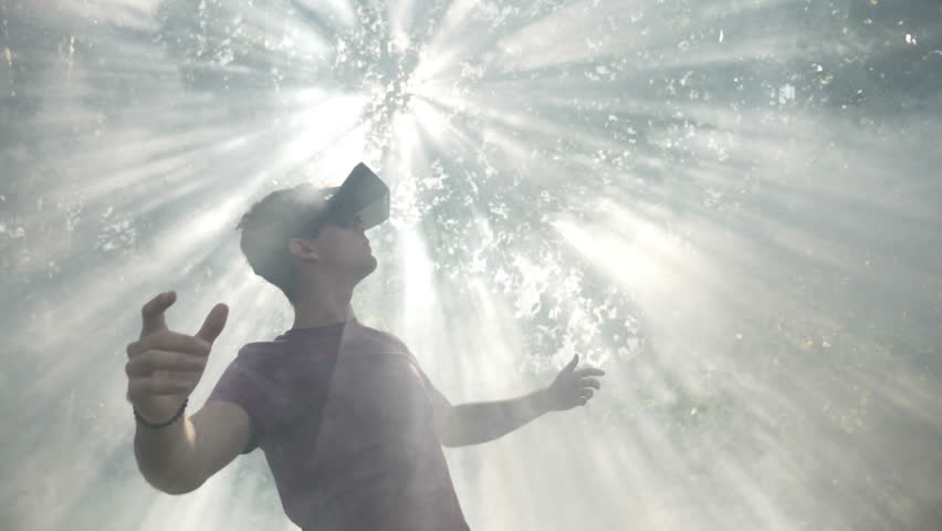 Excited millennial wearing virtual reality VR headset glasses feeling astonished by visual experience exploring cyberspace nature and sun in smoke slow motion | Shutterstock HD Video #33552595