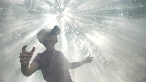 Excited millennial wearing virtual reality VR headset glasses feeling astonished by visual experience exploring cyberspace nature and sun in smoke slow motion