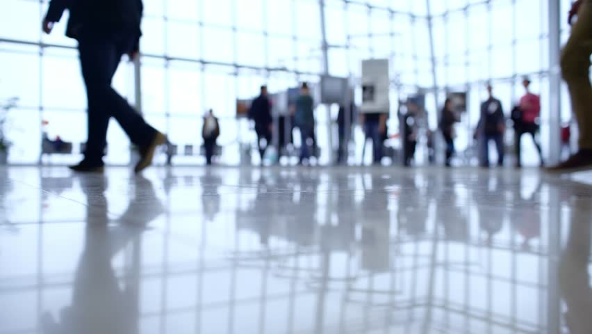 People out of focus walk inside a bright, modern building. Focus in the foreground | Shutterstock HD Video #33557134