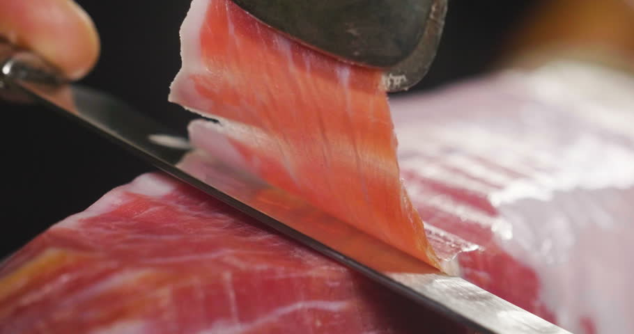 Close up macro of a chef who cuts a slice of ham, of excellent quality, with the knife according to tradition. Concept of: ham, food, Spain and Italy, catering.
