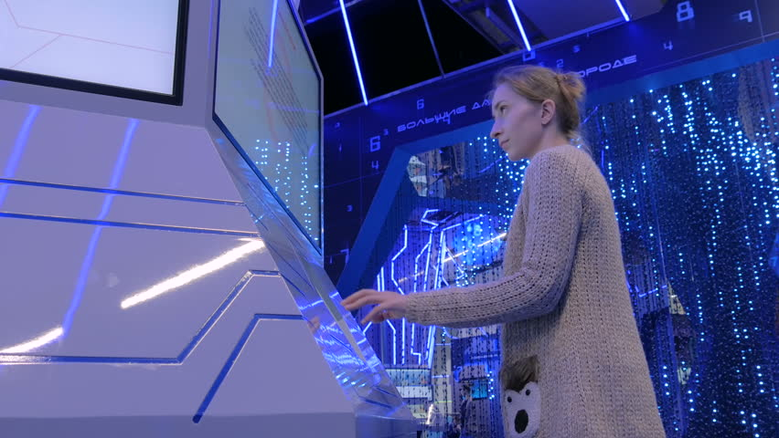 Woman using interactive touchscreen stand and watching video presentation on large display at technology exhibition with futuristic interior #33613825