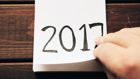 New Year 2018 is coming concept. Hand flips notepad sheet on wooden table. 2017 is turning, 2018 is opening, top view