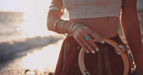 Close-up of young bohemian woman playing the tambourine at beach music festival at sunset