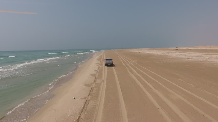 Aerial video trip of rented car driving along sandy beach washed by ocean waves.Footage of travelers having extreme vehicle adventure on seashore during summer journey