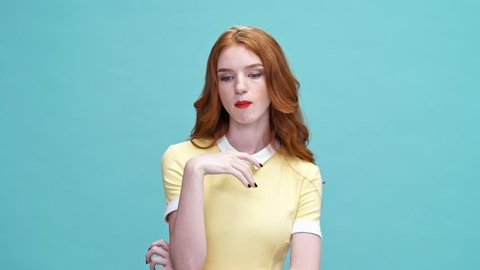 Arrogant ginger woman in dress eating chewing gum and looking away over blue background