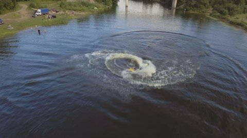 Girl riding a jet ski on the river in a summer sunny day.Aerial view:Teen girl having fun jumping a wave riding yellow and white jet ski in the river.Rider on jet sk rides in a circle on the river