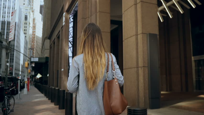 Back view of young businesswoman walking through the financial district of New York, America to office. Slow motion.