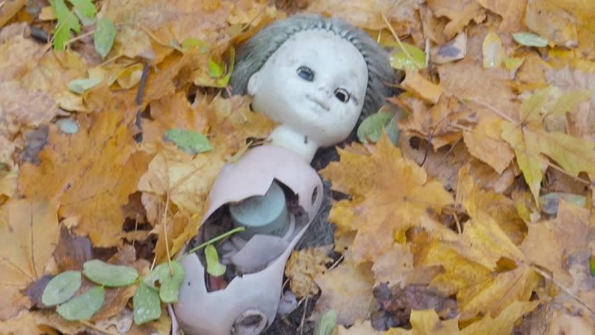 Broken doll toy for childrens lying on autumn fallen leaves in abandoned ghost town Pripyat Ukraine after famous accident at nuclear power plant.