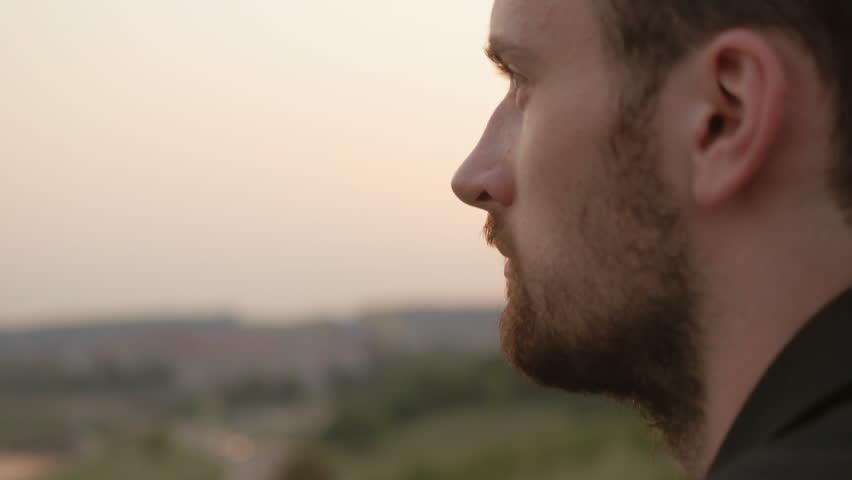 Close-up of young businessman watching panorama of the city. Solid looking entrepreneur thinking about future business projects early in the morning at sunrise outdoors. | Shutterstock HD Video #33670375