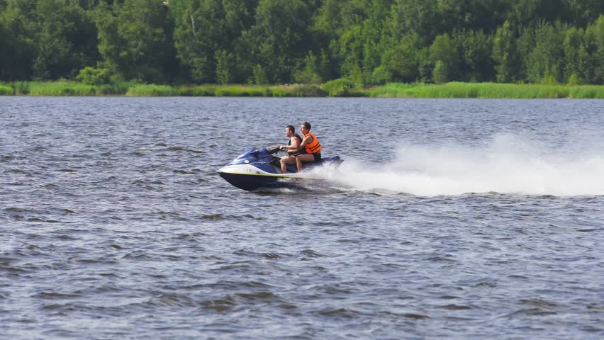 People riding on a jet ski. High speed jetski with water spray. People rid on water scooter. 4k.