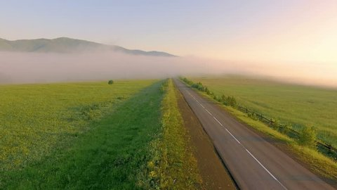 AERIAL:  An empty road in a dense fog against a backdrop of a mountain landscape. Beautiful nature during sunrise. Highway, transportation, outdoor, road trip.