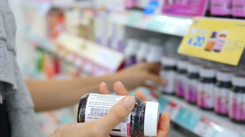 Buying Medicine In Drugstore. Hands Holding Pill Bottles. Closeup. 4K.