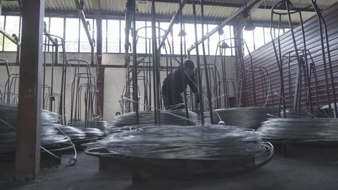 Factory worker control unwinding coils wire during industrial line production of metal mesh fence on heavy mechanical machine in plant, crane shot, tilt up, tracking, concept manufacture, workshop.