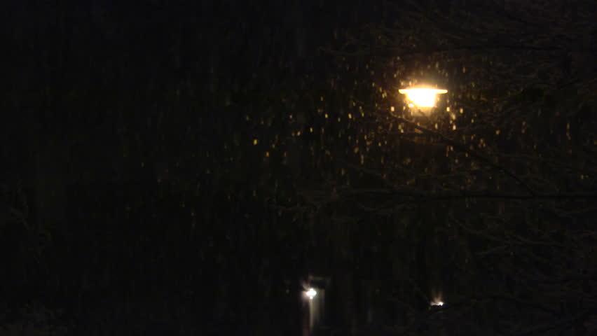 Snow Falling On A Streetlight At Night