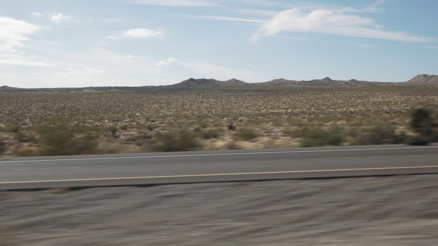 Driving plate side view moving through desert in car empty road
