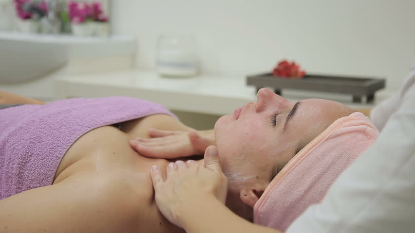 Cosmetologist applies cream on decollete zone of woman in spa salon. She puts gently moisturizer to cleansed decollete and neck skin, with tender massage movements. Experienced specialist dressed in