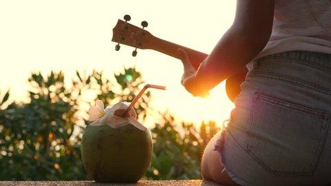 Young Hipster Woman Playing Ukulele Guitar at Beautiful Tropical Beach Sunset. 4K. Thailand.