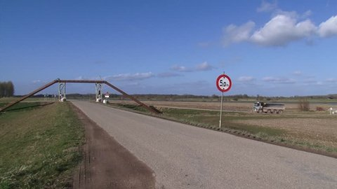 dumper truck passes raised dredging pipes which form a bridge across the old dike of the river ijssel. VEESSEN-WAPENVELD, THE NETHERLANDS - MARCH 2015