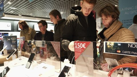 PARIS, FRANCE - CIRCA 2017: Son explaining to mother special offers during Black Friday for the mobiles phones presented on the stand of FNAC French retailer