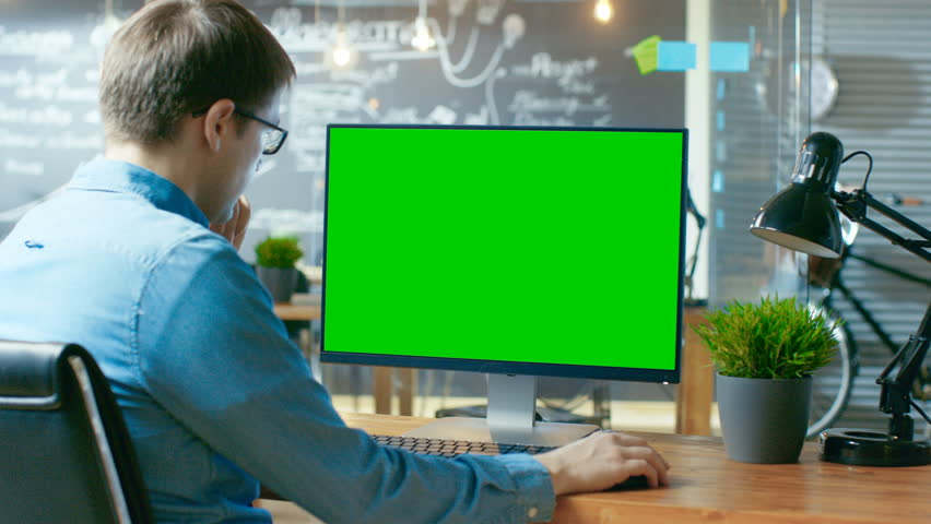 Young Man Works at His Desk on the Personal Computer with Mock-up Green Screen. In the Background His Colleague Works  | Shutterstock HD Video #33748567