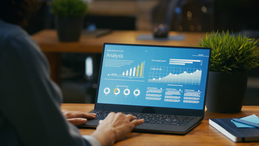 Female Analyst at Her Desk Works on a Laptop Showing Statistics, Graphs and Charts. She Works on the Wooden Table in Creative Office. Over the Shoulder Footage.   | Shutterstock HD Video #33748633