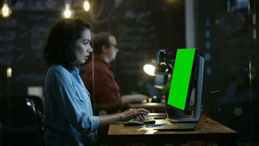 Stressed, Overworked Female Office Employee Holds Her Head in Hands while Working on a Personal Computer with Mock-up Green Screen. In the Background Creative Office  | Shutterstock HD Video #33748699