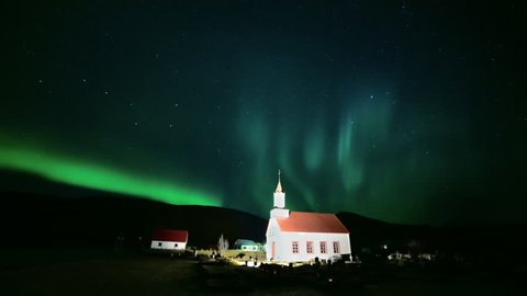 Old small church in winter night - aurora borealis dancing northern lights and moving stars time lapse in Iceland
