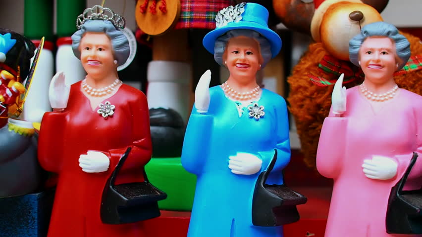 August 2017: figurines of various colors depicting Queen Elizabeth II. The puppet has the hand that moves in salute to greet the Brexit. August 2017 in Edinburgh