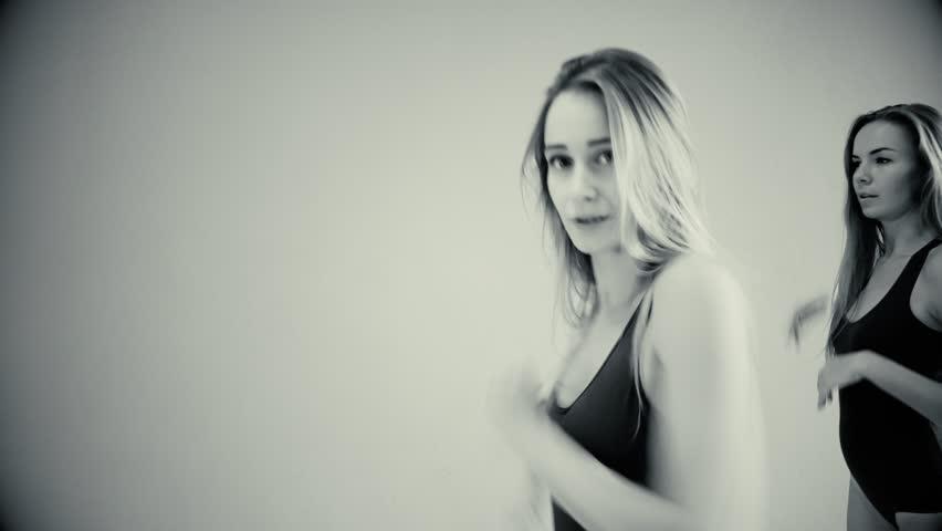 Two girls dance modern dances. Women in swimsuits and leg warmers | Shutterstock HD Video #33784675