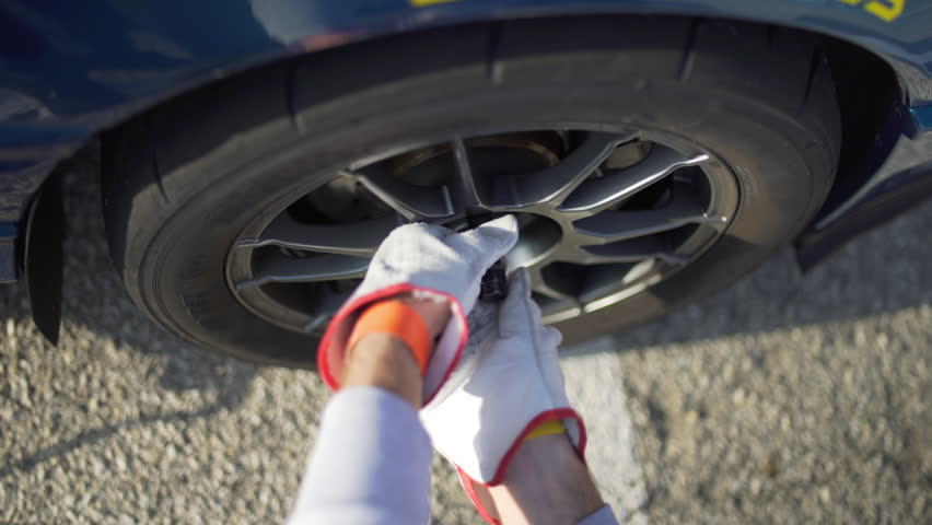 Close up of young man change the tire of his sports car. Mechanic screwing unscrewing the bolt of a car wheel.