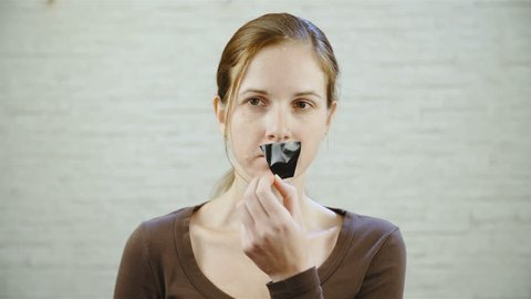 Woman remove tape from mouth 4K. Portrait static shot of brown hair woman in focus looking at the camera can't speak because of black ducktape over mouth. Removing tape by hand. Brick wall background.