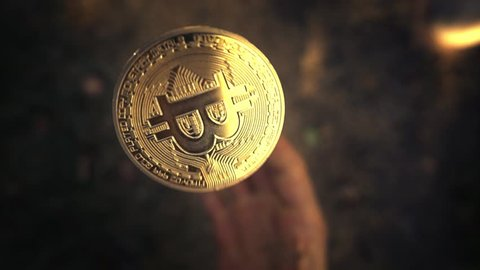 Hand flipping golden bitcoin coin and catching it. Slow motion, closeup.