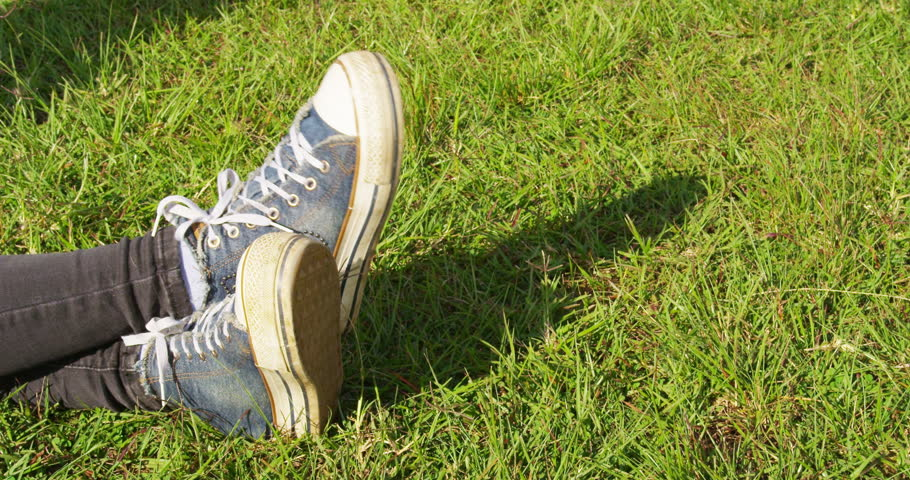 Female legs in blue sneakers are moving along the grass.