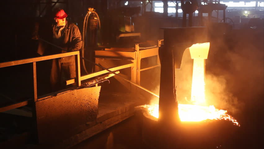 Hard work in the foundry, worker watching and controlling iron smelting in furnaces, too hot and smoky working environment.