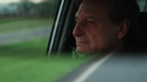Older man seen through car rear view mirror driving on highway road. Sleepy senior man driving on road seen with car mirror at 120fps sunset golden hour time