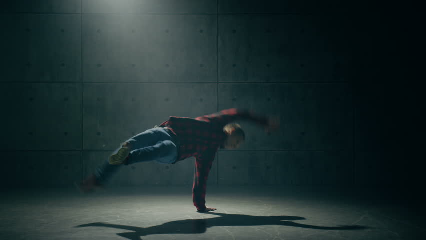 Young man dancing breakdance in studio
