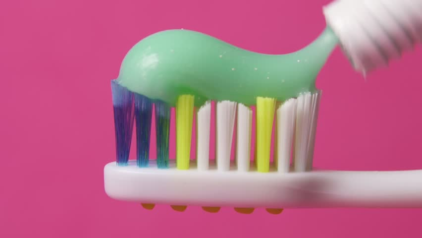 Toothbrush paste on toothbrush over pink background close up. Sequence.
