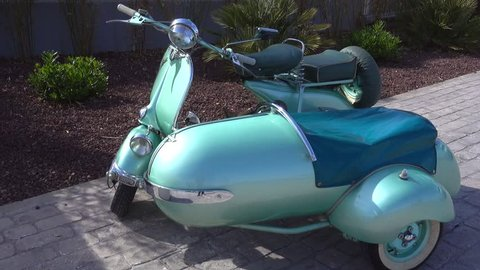 Old vintage green Vespa  scooter (motorcycle) with sidecar parked in the sun
