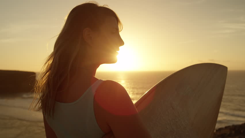 SLOW MOTION LENS FLARE: Lovely young surfer girl looking at golden sunset turns around and faces camera. Woman holding a surfboard, observing at sunset in Fuerteventura, Canary Islands turns around.