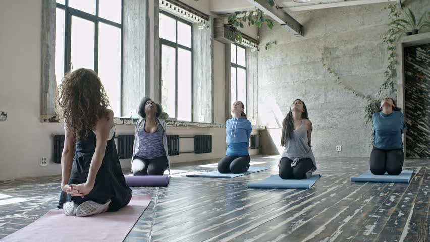 PAN of curly female trainer sitting on yoga mat and showing stretching exercises to multiethnic group of women