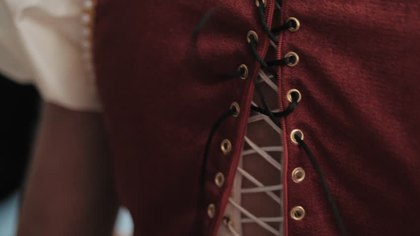 Stylist helps to tighten the corset of a historical dress on woman. 18th century look. Hands close-up. slow motion