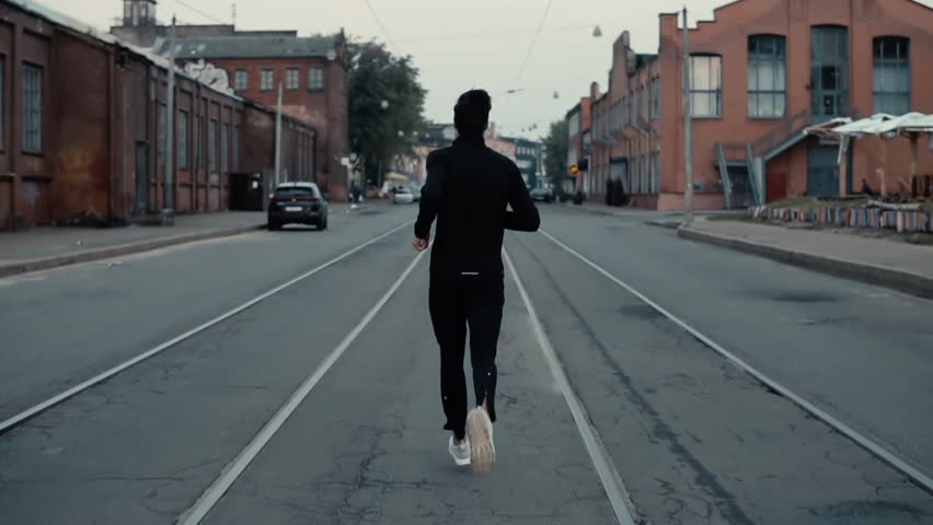 Sportsman running in the middle of the street. Background shot. Slow motion. Back distant view between tram tracks. #33920155