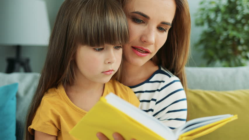 Close up of the mother and daughter scrolling pages of the book and reading. At home. Portrait. Indoor