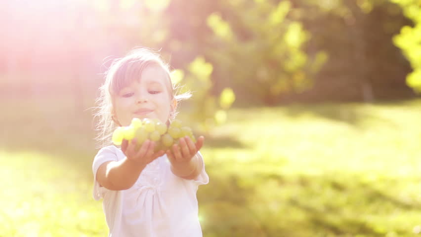 Girl treats the viewer grapes. Slow motion. Lens flare
