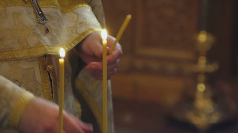 The Sacrament of Baptism in the Orthodox Church. Close-up of a priest lighting candles in a font
