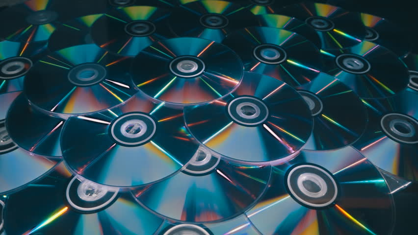 Many compact discs lying on top of each other rotate and shimmer in different colors. On they fall several CDs. Closeup. Slow mo, slo mo, slow motion, high speed camera, 240fps, 250fps