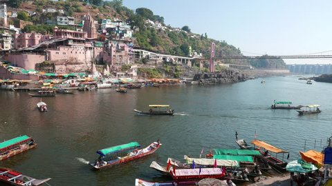 Omkareshwar cityscape, India, sacred hindu temple. Holy Narmada River, boats floating. Travel destination for tourists and pilgrims.