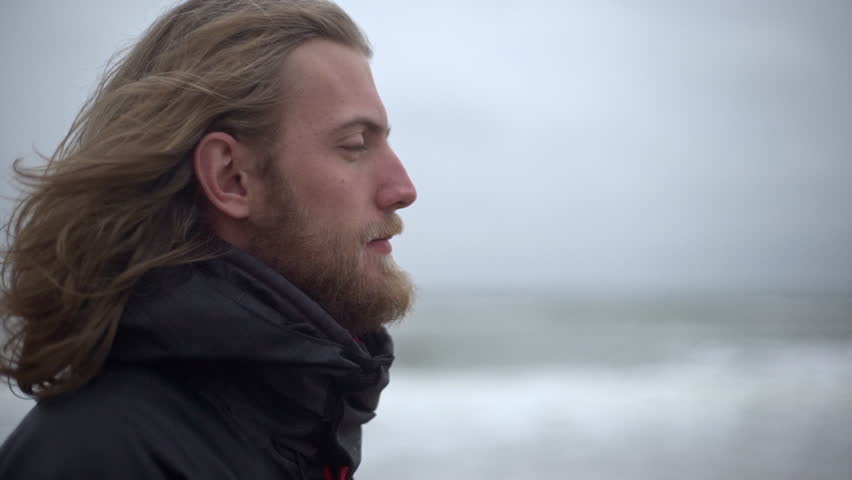 Portrait in profile of manly male explorer with long brown hair taking pleasure in force of nature breathing fresh cold air looking ahead in slow motion